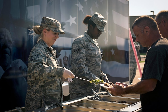 U.S. Air Force Tech. Sgt. Montana Fleissner, left, a services specialist with the 107th Force Support Squadron, New York Air National Guard, and Senior Airman Maya Houston, a services specialist with the 182nd Force Support Squadron, Illinois Air National Guard, serve dinner in Crow Agency, Mont., Aug. 1, 2017. They and six other services specialists provided meal support to 182nd Civil Engineer Squadron Airmen building veterans' homes for the Innovative Readiness Training program. (U.S. Air National Guard photo by Tech. Sgt. Lealan Buehrer)