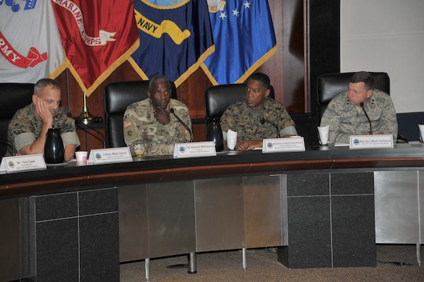 Four generals seated at table, facing viewer.