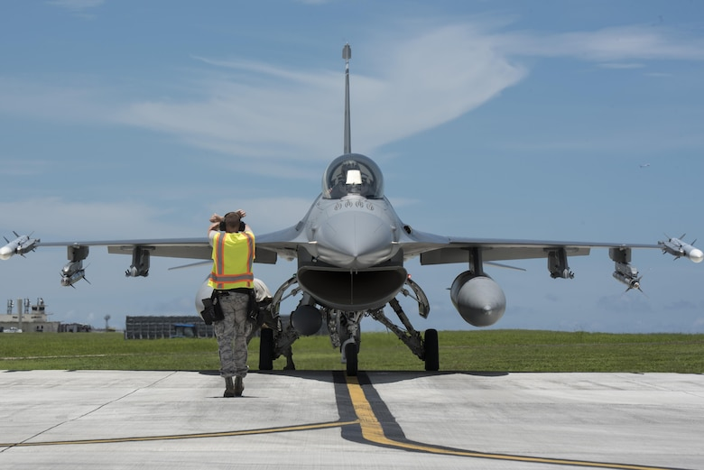 Airman on the flight line directing an F-16 aircraft