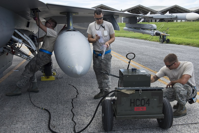 Three Airmen working on an F-16 aircraft
