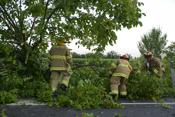 Fabrizio La Marca, Staff Sgt. Jason Holmes and Tech. Sgt. Brian Martenis, 31st Civil Engineer Squadron firefighters, pull debris off a highway Aug. 10, 2017, in Pordenone Province, Italy. The 31st CES firefighters teamed with local first responders to clear roadways after heavy thunderstorms passed through the area. (U.S. Air Force photo by Tech. Sgt. Andrew Satran)