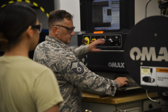 U.S. Air Force Master Sgt. Terry Willis, right, metals technologies section chief assigned to the 927th Maintenance Squadron (MXS), trains Airman 1st Class Katherine Dawson, metals technologies apprentice assigned to the 6th MXS, on how to use the OMAX water-jet cutting machine at MacDill Air Force Base, Fla., Aug. 7, 2017. The 927th MXS is the associate reserve unit embedded with the 6th MXS to fabricate essential parts, keeping the KC-135 Stratotanker aircraft in the air. (U.S. Air Force Photo by Staff Sgt. Adam C. Borgman)