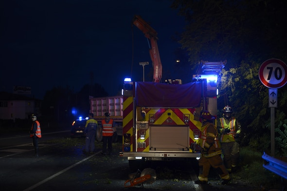 Staff Sgt. Jason Holmes and Tech. Sgt. Brian Martenis, 31st Civil Engineer Squadron firefighters, prepare to remove a tree from a highway Aug. 10, 2017, in Pordenone Province, Italy. The 31st CES firefighters teamed with local first responders to clear roadways after heavy thunderstorms passed through the area. (U.S. Air Force photo by Tech. Sgt. Andrew Satran)