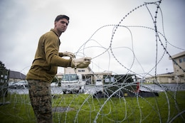 Pfc. James P. Gross, a radio and satellite communications operator, places barbed wire on the ground at Misawa Air Base, Japan, August 10, 2017, signifying the start of exercise Northern Viper 2017. This exercise tests the interoperability and bilateral capability of the Japan Ground Self-Defense Force and U.S. Marine Corps forces to work together and provides the opportunity to conduct realistic training in an unfamiliar environment. Gross, a Milwaukee native, is with Marine Wing Communications Squadron 18, Marine Air Control Group 18, 1st Marine Aircraft Wing. (U.S. Marine Corps photo by Lance Cpl. Andy Martinez)
