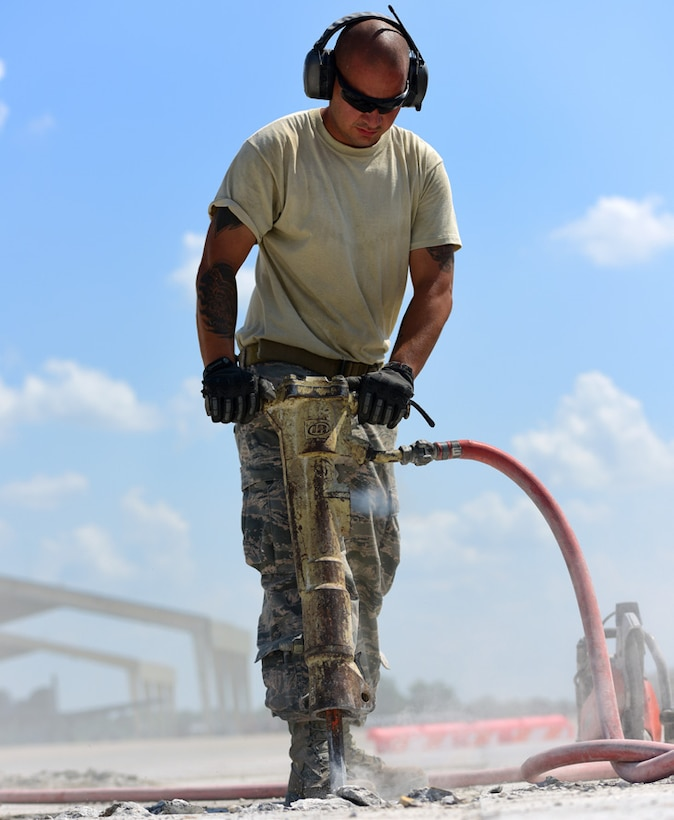 """U.S. Air Force Staff Sgt. Warocz, a 509th Civil Engineer Squadron pavement and equipment shop supervisor, uses a jack hammer at Whiteman Air Force Base, Mo., July 25, 2017. Members of the shop, known as """"Dirtboyz,"""" refurbished 19 yards of concrete on the flightline, enabling taxiway K to be operational again."""