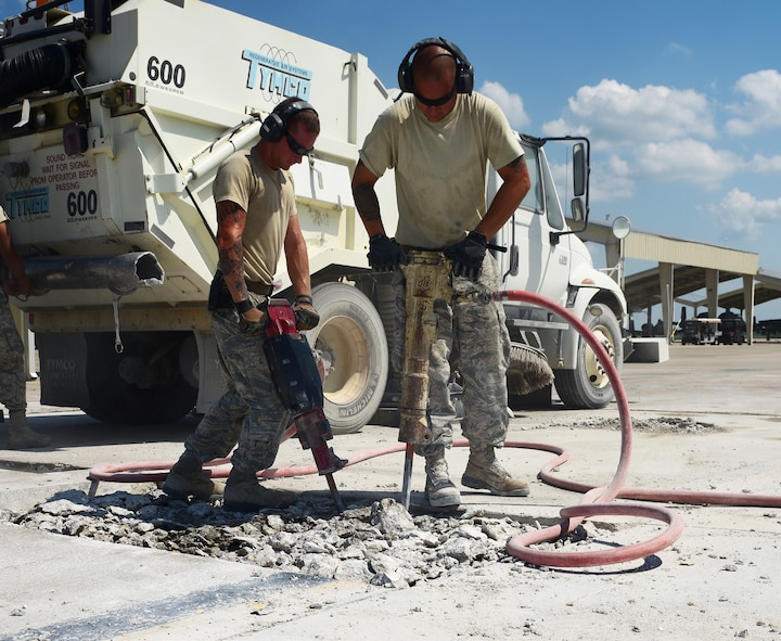 U.S. Air Force Staff Sgt. Dozzi, left, and Staff Sgt. Warkocz, 509th Civil Engineer Squadron pavement and equipment shop supervisors, use jack hammers to break cement apart on the flightline at Whiteman Air Force Base, Mo., July 25, 2017. First, the Dirtboyz cut sections of spalled concrete with a K-12 concrete saw then jack hammer the ground to break it into small enough pieces for the airfield sweeper to remove the debris.