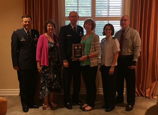 Joining 2017 Air Force Fisher House Volunteer of the Year Dede Richardson, center, Aug. 7 to celebrate her accomplishment were, left to right, Col. Bradley McDonald, 88th Air Base Wing commander; Karen Healea, Fisher Houses manager; Maj. Gen. Duke Richardson, Air Force program executive officer for Presidential Airlift Recapitalization, Air Force Life Cycle Management Center; Col. Shari Silverman, 88th Medical Group commander; and Dan Druzbacky, 88 MDG compassionate care manager. The award ceremony was held at the Fisher House II, one of two, side-by-side compassionate comfort care facilities at Wright-Patterson Air Force Base. (Skywrighter photo/Amy Rollins)