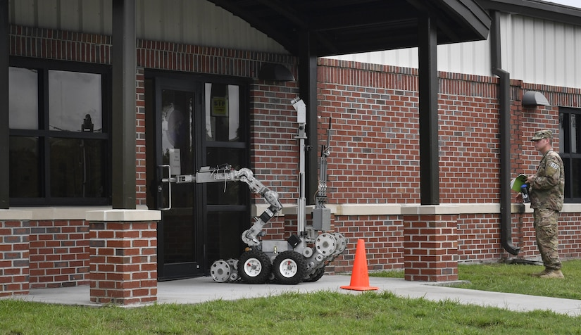 Tech. Sgt. Jonathan Morrison, 628th Civil Engineer Squadron explosive ordnance disposal technician, observes a robot inspecting the base mail center's entrance during an anti-terrorism exercise here, Aug. 9, 2017. The 628th EOD flight responded to a scenario and used the robot to search a simulated suspicious package during the exercise.