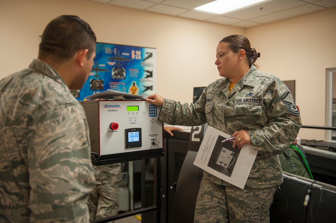 Master Sgt. Jennifer Flecker, 9th Physiological Support Squadron support flight chief, runs through the initial process of turning on and preparing a Reduced Oxygen Breathing Device for a hypoxia demonstration.