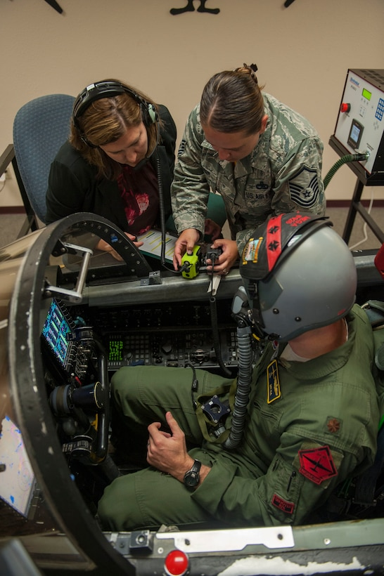 Master Sgt. Jennifer Flecker, 9th Physiological Support Squadron support flight chief, sets up the communication connection between the pilot and the rest of the support staff who will be monitoring the pilots vitals and the conditions of the simulation.