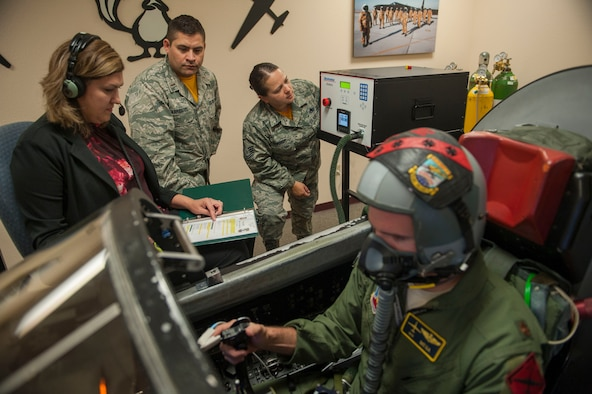 9th Physiological Support Squadron personnel monitor a pilot's vitals and cognitive abilities as he flies a simulated mission using the Reduced Oxygen Breathing Device at Beale Air Force Base, California, July 21, 2017. The ROBD allows for a more efficient and safer way for pilots to train in simulated environments. (U.S. Air Force photo/Senior Airman Justin Parsons)