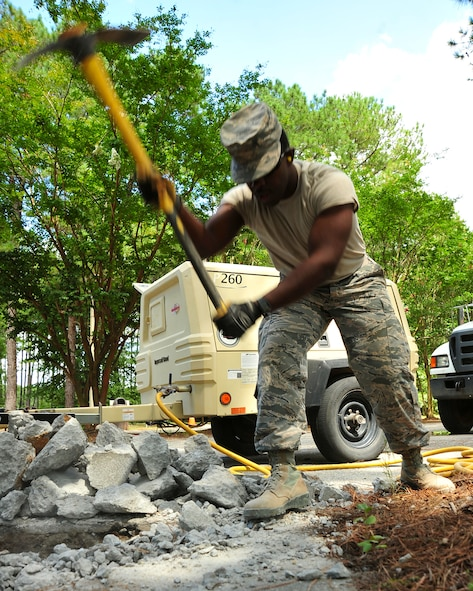 U.S. Air Force Airman 1st Class Davon Thompson, 20th Civil Engineer Squadron pavement and construction equipment apprentice, uses a pickaxe to separate pieces of concrete from the ground at Shaw Air Force Base, S.C., Aug. 10, 2017. After the pieces were loosened, they were moved by hand and set aside for disposal. (U.S. Air Force photo by Airman 1st Class Kathryn R.C. Reaves)