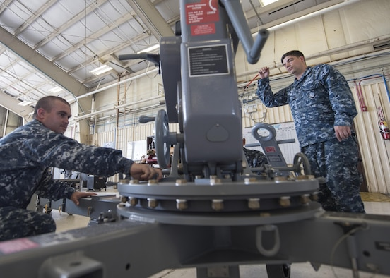 "U.S. Navy Aviation Support Equipment Technician Second Class Eric Stark, right, 33rd Maintenance Squadron Aerospace Ground Equipment, demonstrates how to operate a portable floor crane for Aviation Support Equipment Technician First Class Jerimiah Appel, USS Abraham Lincoln (CVN-72), Aug. 9, 2017, at Eglin Air Force Base, Fla. Appel is one of two AS1s who are receiving ""Phase 1"" initial training for F-35 support systems from the 33rd MXS. The information he is learning will be used to operate and maintain the machines that supply electricity, air pressure and hydraulic pressure to the aircraft when the engine is not running. (U.S. Air Force photo by Staff Sgt. Peter Thompson)"