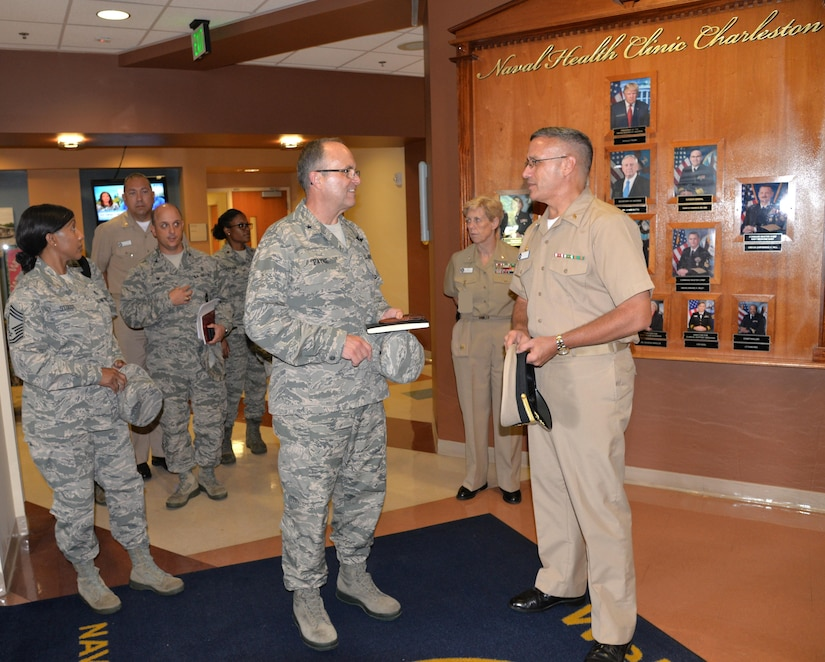 Naval Health Clinic Charleston Commanding Officer Capt. Dale Barrette, right, highlights the services available at NHCC with Air Force Brig. Gen. Lee Payne, Air Mobility Command Surgeon, center, and Chief Master Sgt. Sonya Stoute, left, AMC Medical Enlisted Force Chief, as they tour NHCC during their visit to Joint Base Charleston July 25.