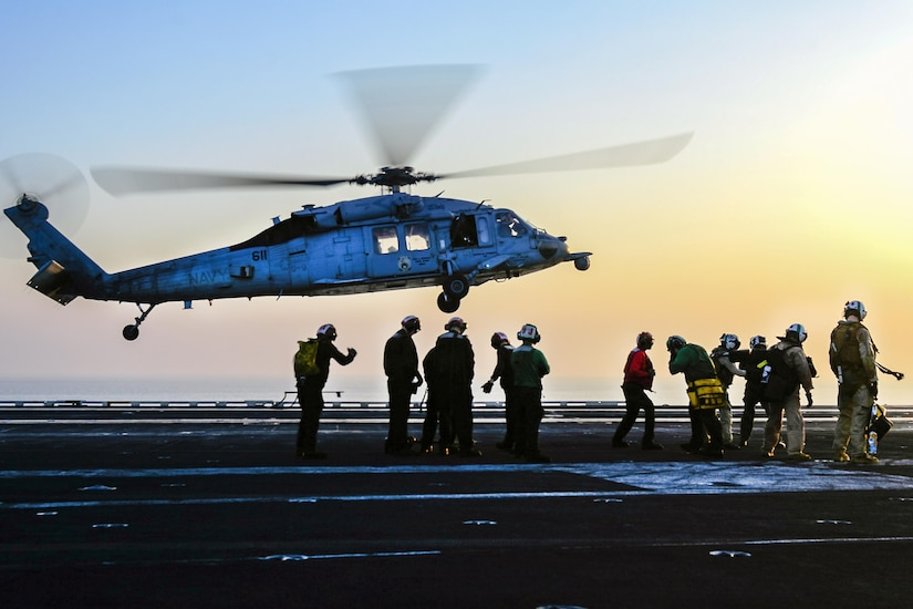 Troop stand on a ship's flight deck as a helicopter comes in for a landing.