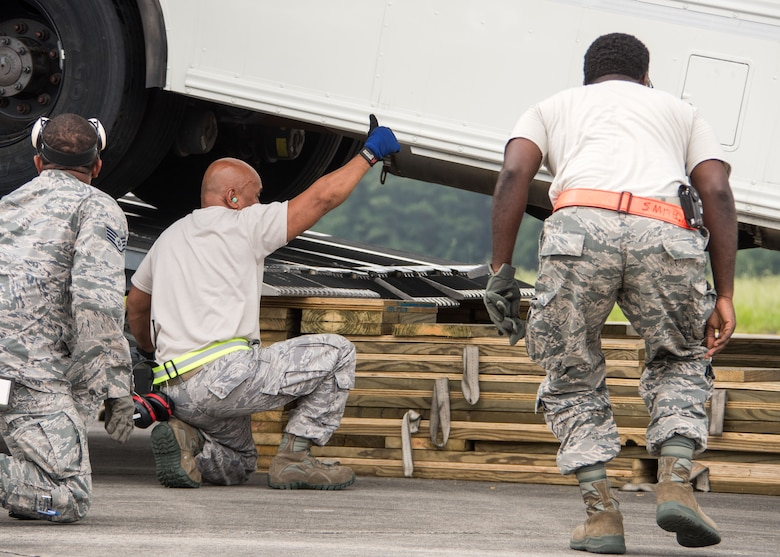 An aerial porter gives a thumbs up to the driver of a bus as it's backed onto the cargo bay of a C-17 Globemaster III at Dobbins Air Reserve Base, Ga. Aug. 7, 2017. During the exercise, units such as the aerial port, were comprised of Airmen from different units around Air Force Reserve Command to simulate a workforce that might be expected in a deployed environment. (U.S. Air Force photo/Staff Sgt. Andrew Park)
