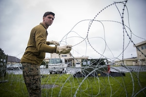 Pfc. James P. Gross, a radio and satellite communications operator, places barbed wire on the ground at Misawa Air Base, Japan, August 10, 2017, signifying the start of exercise Northern Viper 2017. This exercise tests the interoperability and bilateral capability of the Japan Ground Self-Defense Force and U.S. Marine Corps forces to work together and provides the opportunity to conduct realistic training in an unfamiliar environment. Gross, a Milwaukee native, is with Marine Wing Communications Squadron 18, Marine Air Control Group 18, 1st Marine Aircraft Wing.
