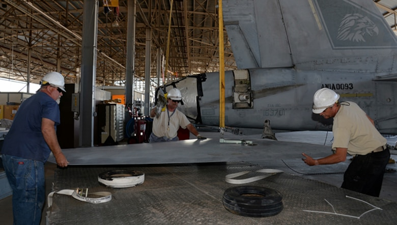 309th Aerospace Maintenance and Regeneration Group mechanics carefully place a removed stabilator from an F/A-18C Hornet at Davis-Monthan AFB, Ariz., on June 6, 2016, onto a transport cart as part of the preparation to transport the aircraft to a Boeing maintenance facility at Cecil Airport, Jacksonville, Fla.