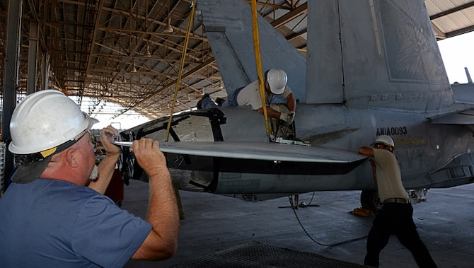 309th Aerospace Maintenance and Regeneration Group mechanics work to remove a stabilator from an F/A-18C Hornet at Davis-Monthan AFB, Ariz., on June 6, 2016, in preparation for the aircraft to be transported to a Boeing maintenance facility at Cecil Airport in Jacksonville, Fla.