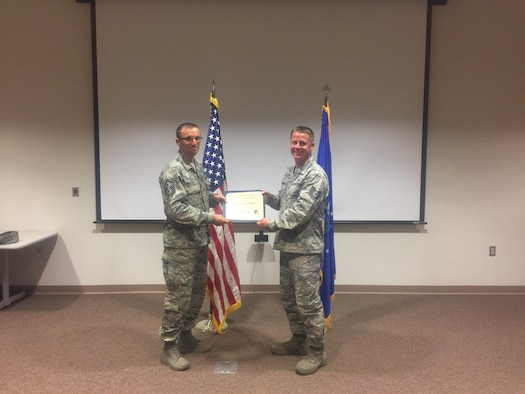 Tech. Sgt. Brandon Rankin, a 372nd Training Squadron, Detachment 10 technical training instructor, receives the June Top III noncommissioned officer award from Master Sgt. William Wallick, the 54th Aircraft Maintenance Squadron first sergeant, Aug. 2, 2017, at Holloman Air Force Base, N.M. During the month of June, Rankin accumulated 112 teaching hours over 14 days of instruction. His efforts led to the early graduation of eight students, sustaining manning requirements for six major commands. He became qualified to facilitate the new Airmanship 300 course for first term Airmen. (Courtesy photo)