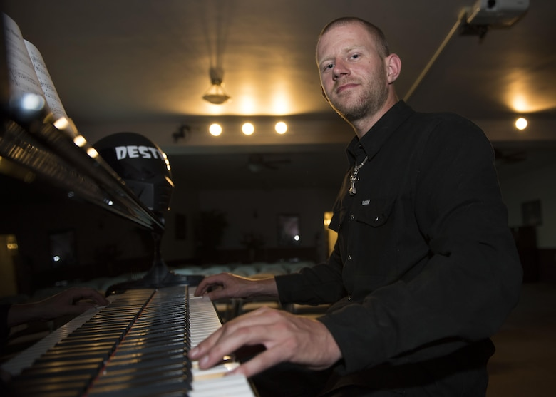 Senior Airman Logan Lingren, 92nd Maintenance Squadron aircraft structural maintenance journeyman, pauses for a photo while playing a grand piano July 24, 2017, in Spokane, Washington. Lingren helped save a man from a knife-wielding attacker in 2016 and was chosen to be in the Portraits of Courage, an Air Force program that highlights Airmen who display exceptional valor. (U.S. Air Force photo/ Airman 1st Class Ryan Lackey)