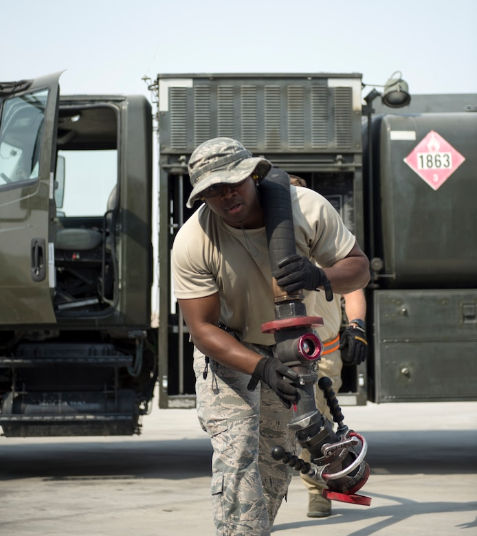 U.S Air Force Tech. Sgt. Jason Johnson, a fuels specialist with the 379th Expeditionary Logistics Readiness Squadron, Fuels Management Flight, carries a fuel hose at Al Udeid Air Base, Qatar, July 24, 2017.