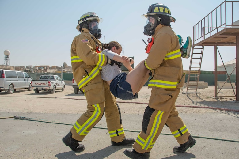 A team of firefighters perform a two-man carry during a victim extraction during a training scenario Friday, August 11, 2017, at the PERSCO building at an undisclosed location in Southwest Asia. (U.S. Air Force photo by 1st Lt. Rashard Coaxum)