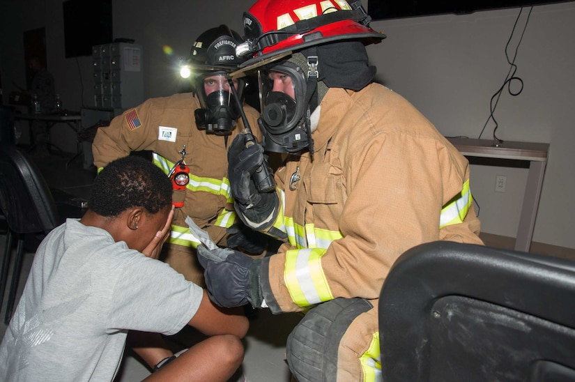 Two firefighters asess the condition of a simulated victim prior to extracting her from the building during a fire response exercise Friday, 11 August 2017, at an undisclosed location in Southwest Asia. (U.S. Air Force photo by Master Sgt. Eric M. Sharman)