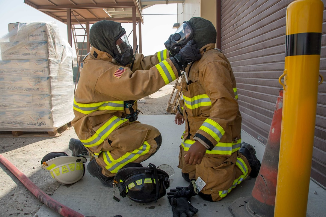 Master Sgt. Aaron Culwell (left), the 386th Expeditionary Civil Engineer squadron fire station one station captain performs a gear safety check of a teammate during a training scenario Friday, August 11, 2017, at the PERSCO building at an undisclosed location in Southwest Asia. (U.S. Air Force photo by 1st Lt. Rashard Coaxum)