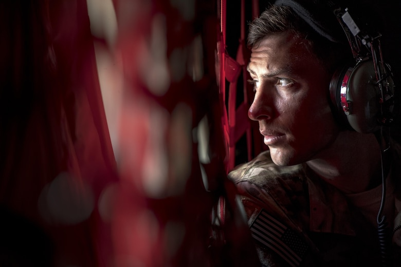 1st Lt. David Schmidt, 71st Rescue Squadron combat systems officer, looks out the window of an HC-130J Combat King II during Stealth Guardian, Aug. 9, 2017, in the skies over the Apalachicola National Forest, Fla.