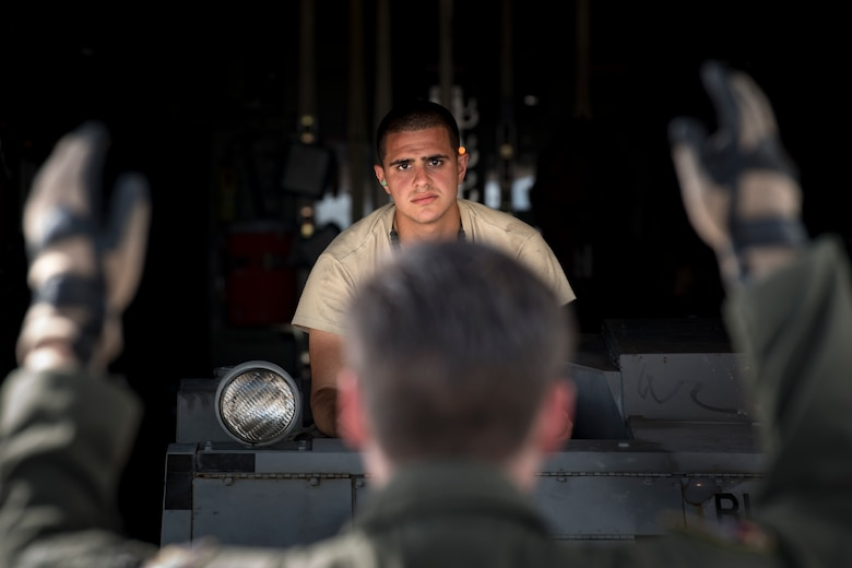 A weapons Airman from the 325th Fighter Wing looks toward a loadmaster from the 71st Rescue Squadron while loading equipment onto an HC-130J Combat King II, Aug. 9, 2017, at Tyndall Air Force Base, Fla.