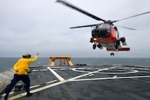 "MST1 Sean Carrillo gives the ""take-off"" signal to the HH-60 during flight operations."