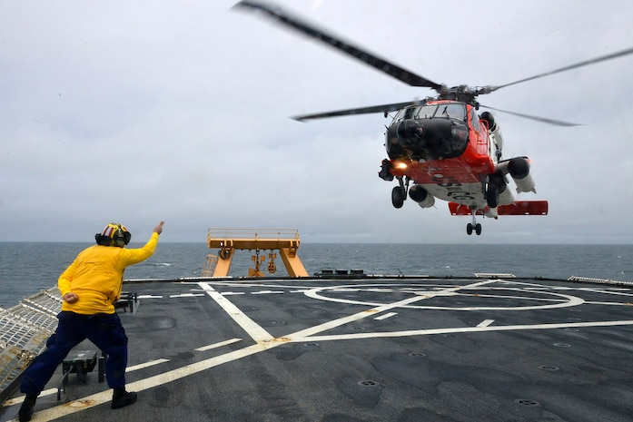 """MST1 Sean Carrillo gives the """"take-off"""" signal to the HH-60 during flight operations."""