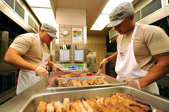 U.S. Air Force Tech. Sgts. Joshua Leon Guerrero, left, and Nicolas Garrido, both services craftsmen assigned to the 254th Force Support Squadron, Guam Air National Guard, prepare a lunch entree at the Two Seasons dining facility, Aug. 9, 2017, during RED FLAG-Alaska (RF-A) 17-3, at Eielson Air Force Base, Alaska. The 254 FSS team was tasked to augment the 354 FSS during RF-A 17-3. (U.S. Air Force photo by Staff Sgt. Jerilyn Quintanilla)