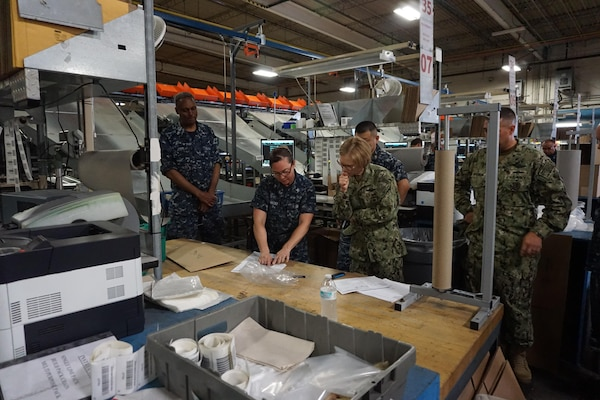 A group of people gathered around a worktable in a distribution warehouse observe someone using a shipping label and other shipping supplies in a demonstration.