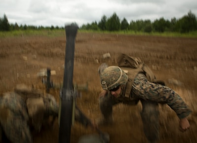 Marine Corps Lance Cpl. Matthew Daily ducks after dropping a round into an M252 81 mm medium weight mortar system