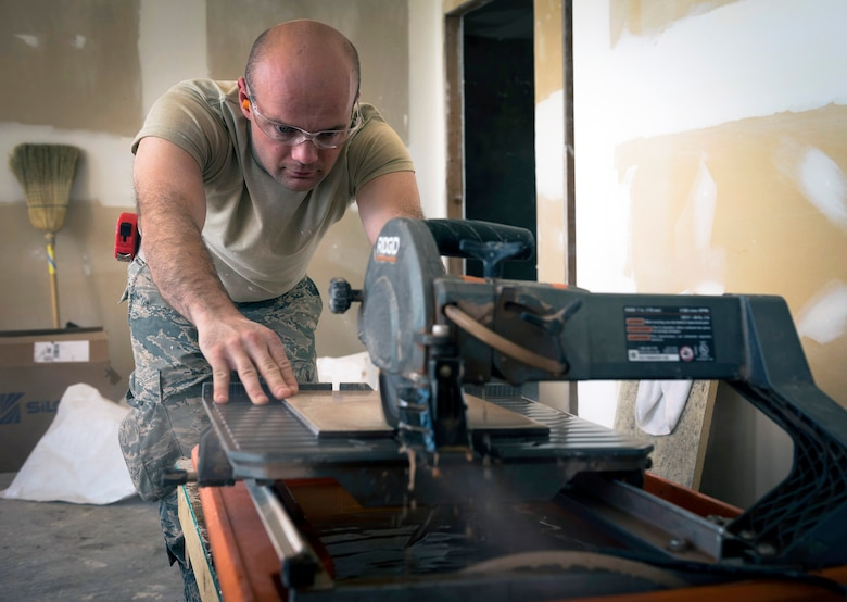 U.S. Air Force Staff Sgt. Corey Buerkman, an engineering craftsman with the 182nd Civil Engineer Squadron, Illinois Air National Guard, cuts ceramic floor tile in Crow Agency, Mont., July 27, 2017. The squadron helped build homes for Crow Nation veterans as part of the Department of Defense's Innovative Readiness Training civil-military relations program. (U.S. Air National Guard photo by Tech. Sgt. Lealan Buehrer)