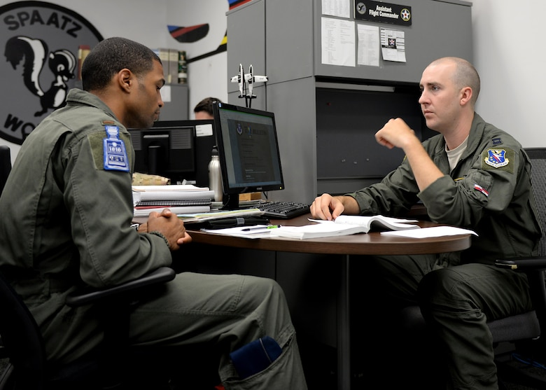 Second Lt. Marcos Marrero-Disla, a 41st Flying Training Wing student pilot, and Capt. Calogero San Filippo, the 41st FTS Assistant Flight Commander, run through a flight plan Aug. 8, 2017, on Columbus Air Force Base, Mississippi. Talking through flight plans and scenarios helps pilots develop solutions and prepare them for creating real flight plans. (U.S. Air Force photo by Airman 1st Class Keith Holcomb)
