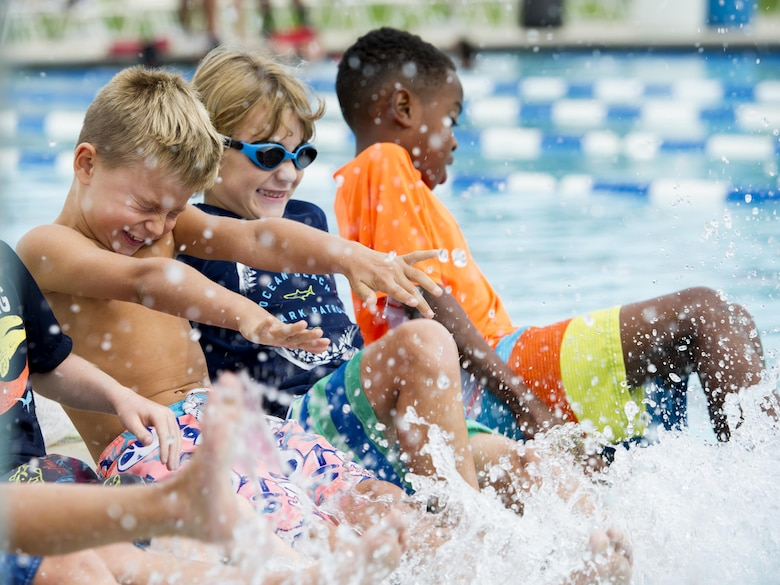 Children kick their feet in the base pool.