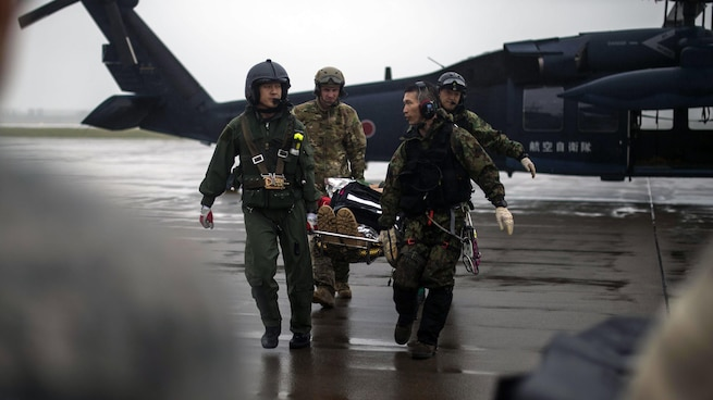 MISAWA AIR BASE, Japan (Aug. 9, 2017) - U.S. Air Force Tech. Sgt. Jason Allchin, a 35th Operations Support Squadron survival, evasion, resistance and escape specialist, and Japan Air Self-Defense Force Akita Prefecture Rescue Squadron pararescuemen and aircrew transport a simulated injured pilot during exercise Cope Angel 17 at Misawa Air Base. Once sending his location, rescue crews retrieved and transported the simulated injured pilot by a UH-60J Black Hawk back to Misawa AB. The purpose of this exercise showcased the bilateral alliance between the U.S. and Japan during possible rescue and triage operations.