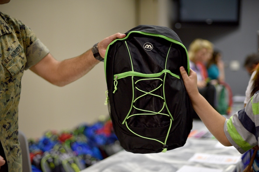 asp U.S. Marine Sgt. Nathen Gruden, 312th Training Squadron instructor, gives a free backpack full of school supplies to a child during Operation Back to School in the Event Center on Goodfellow Air Force Base, Texas, Aug. 10, 2017. The backpack included pencils, pens, notebooks and crayons. (U.S. Air Force photo by Airman 1st Class Randall Moose/Released)