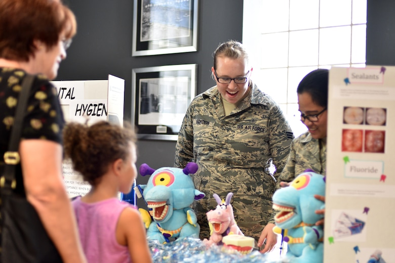 U.S Air Force Senior Airman Ariana Gordon, 17 Medical Operation Squadron dental assistant, demonstrates dental hygiene to a military family during Operation Back to School in the Event Center on Goodfellow Air Force Base, Texas, Aug. 10, 2017. The 17th Medical Group also provided child physicals at the clinic to ensure the children's medical records are up to date. (U.S. Air Force photo by Airman 1st Class Randall Moose/Released)