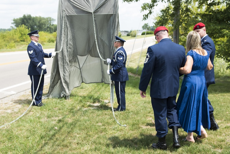 Senior Master Sgt. Bradford Greisen, 320th Special Tactics Squadron, and Col. Michael Martin, commander of the 24th Special Operations Wing, escort Sheila McDaniel to unveil a highway sign during a ceremony dedicating a six-mile stretch of Highway 121 in honor of her son, Master Sgt. William L. McDaniel II, in Greenville, Ohio, Aug. 14, 2017. McDaniel was part of a joint, special operations team who were infiltrating an island in Southern Philippines when the MH-47 Chinook helicopter he was in crashed into the Sulu Sea Feb. 22, 2002. (U.S. Air Force photo by Wesley Farnsworth)