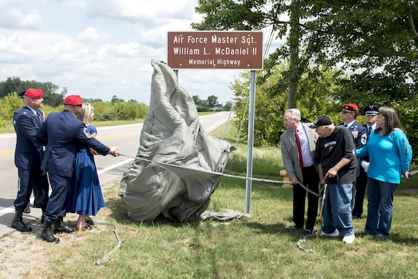 Family and friends of Master Sgt. William L. McDaniel II, unveil a highway sign during a ceremony dedicating a six-mile stretch of Highway 121 in honor of his namesake, in Greenville, Ohio, Aug. 14, 2017. McDaniel was part of a joint, special operations team who were infiltrating an island in Southern Philippines when the MH-47 Chinook helicopter he was in crashed into the Sulu Sea Feb. 22, 2002. (U.S. Air Force photo by Wesley Farnsworth)
