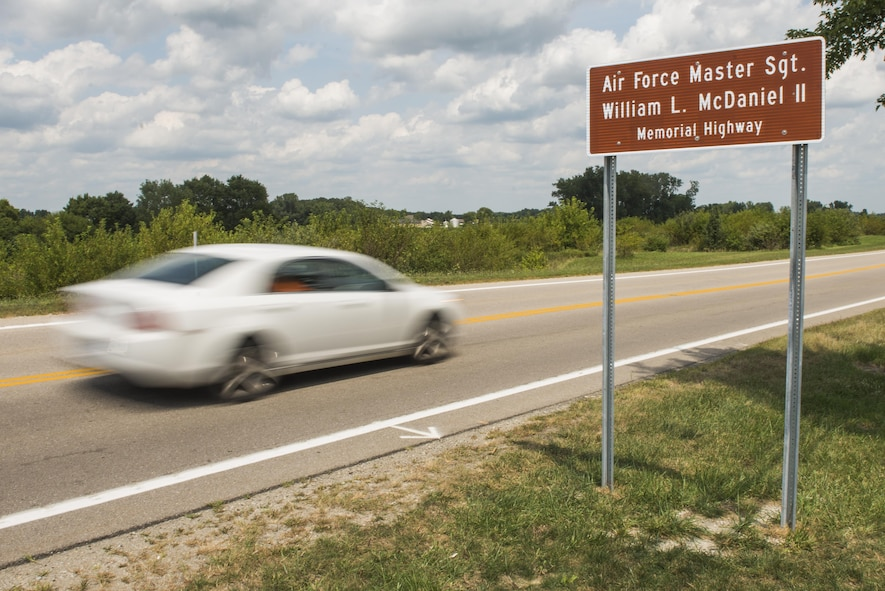 A car drives by the newly unveiled highway sign following a ceremony dedicating a six-mile stretch of Highway 121 in honor of Master Sgt. William L. McDaniel II's namesake in Greenville, Ohio, Aug. 14, 2017. McDaniel was a a Special Tactics pararescueman who was killed when the MH-47 Chinook helicopter he was in crashed in the Philippines Feb. 22, 2002. A pararescueman's unique technical rescue skill sets are utilized during humanitarian and combat operations; they deploy anywhere, anytime, employ air-land-sea tactics into restricted environments to authenticate, extract, treat, stabilize and evacuate injured or isolated personnel. (U.S. Air Force photo by Wesley Farnsworth)