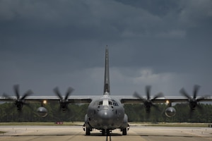 An HC-130J Combat King II aircraft taxis on a runway.