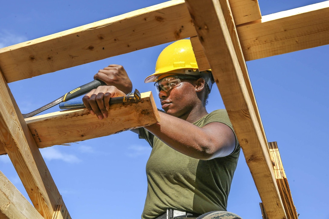 A Marine wearing a hard hat uses tools to help build a wooden structure.