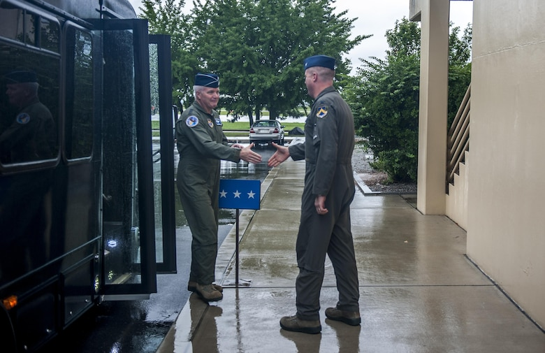 """Lt. Gen. Jerry """"JD"""" Harris, Chief of Staff for Strategic Plans and Requirements, Headquarters U.S. Air Force, Washington, D.C, steps off the bus to shake hands with Col. David """"Wolf"""" Shoemaker, 8th Fighter Wing commander, at Kunsan Air Base, Republic of Korea, Aug. 14, 2017. Gen. Harris, the 48th """"Wolf"""" recounted his time as commander of the 8th FW during his visit and toured multiple squadrons around the installation. Visits of this type enable proactive advocacy at the Pentagon regarding issues and best practices specific to the unique mission on the Korean Peninsula and the Wolf Pack's capabilities which support the overall U.S. Forces Korea mission here. (U.S. Air Force photo by Senior Airman Colville McFee)"""