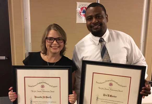 Facing viewer, woman and man in business attire posing with framed awards.