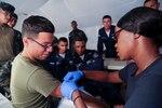A U.S. Navy Hospital Corpsman prepares to take a blood sample from a U.S. Marine as Honduran troops look on.